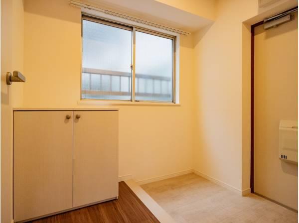 落ち着いた色を基調としていて、優しい印象の明るい玄関スペース。
